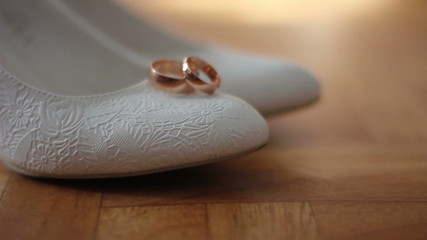 white female shoes with wedding rings. dolly shot