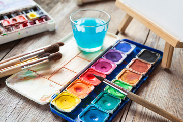 Set of watercolor paints, art brushes, glass of water and easel