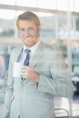 Businessman holding cup of coffee through the window
