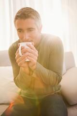 Smiling man drinking hot beverage