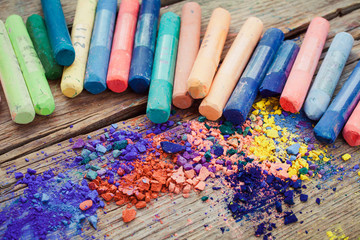 Collection of rainbow colored pastel crayons with pigment dust.