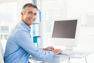 Smiling man typing on keyboard and looking at camera