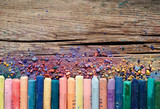 Fototapety Pastel crayons and pigment dust on rustic wooden background.