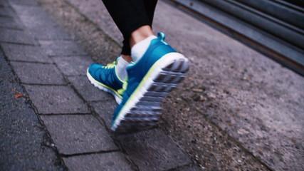Closeup of woman's feet running in slow motion on asphalt