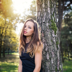 Intense young woman close up fashion portrait outdoors in a park