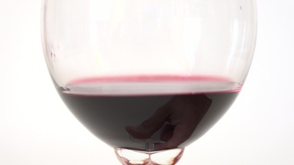 Hand moving a glass of red wine for degustation