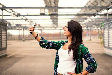 Beautiful teenager taking a selfie with mobile phone outdoors in