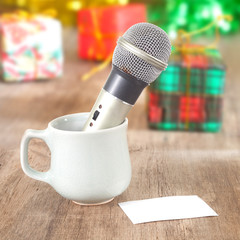 Silver microphone in cup with white note