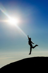 Man Silhouette jumping reaching the sun at the top of the world
