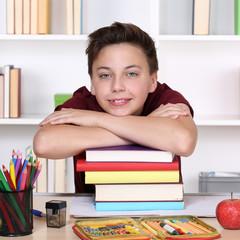 Lachender Schüler und ein Stapel Bücher in der Schule