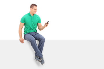 Young man looking at a cell phone seated on panel