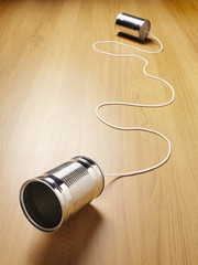 Two tin cans joined with a cord on a wooden background