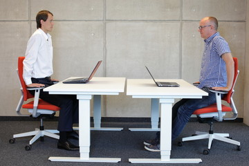 two coworkers exercising on armchairs at  workstations in office