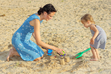 Mom with a baby girl playing in the sand on the beach