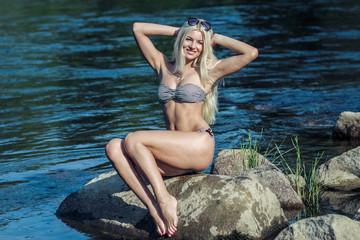 Attractive young blonde woman in a bikini sitting near the water