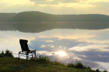 equipped place for fishing with a seat at sunrise with fog.
