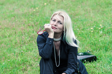 Beautiful older woman in vintage black suit sitting on the grass