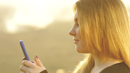 The red head teen girl send message by phone at sunset time