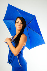 Attractive brunette with blue umbrella and blue dress