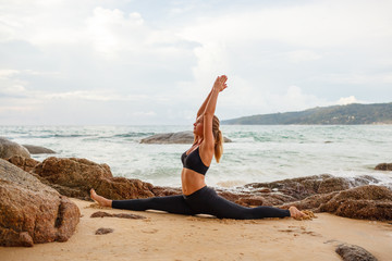 women doing yoga with the ocean behind