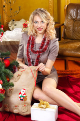 Beautiful  girl with the present near the Christmas tree