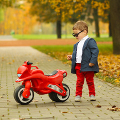 cute little biker on road with motorcycle.