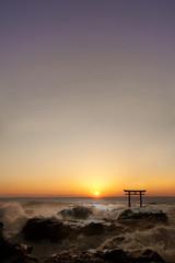 鳥居と波しぶきの日の出
