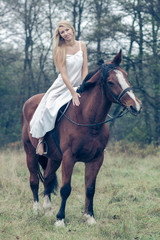 romantic sensual girl in white dress on a horse in the forest