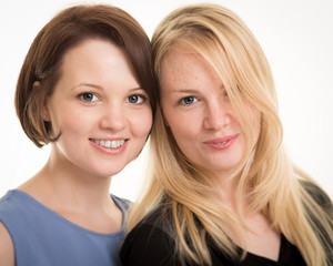 Two Beautiful Smiling Sisters Against A White Background