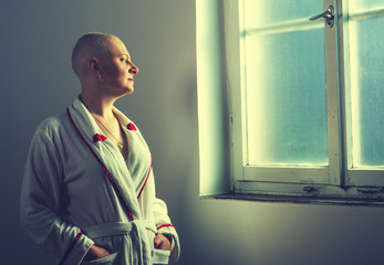 Bald woman suffering from cancer looking throught the hospital w