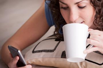girl enjoying her mobile while drinking from a mug