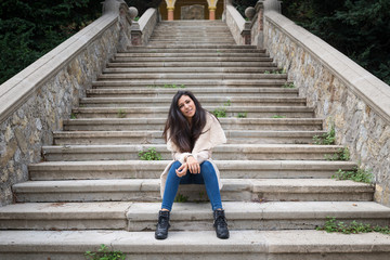 Smiling young woman portrait outdoors sit on stairs in autumn.