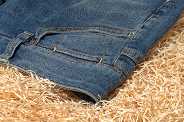 Part of blue jeans lying on straw