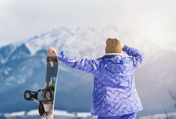 Active girl with snowboard on the snow mountain view