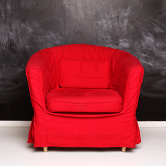 Red conceptual armchair on abstract empty blackboard background