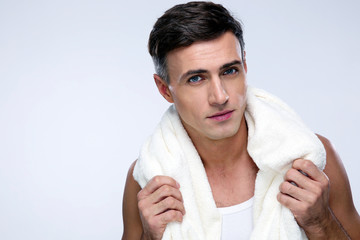 Portrait of a handsome man with towel over gray background