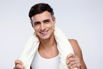 happy standing man with towel over gray background