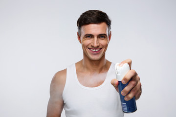 Smiling man spraying deodorant over gray background