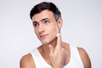 Handsome man putting on cream lotion on face