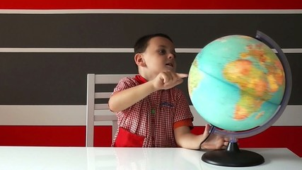 Children in school uniform spinning globe learning geography