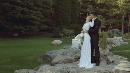 Enamoured newlyweds standing among green park