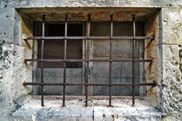 Piccola finestra vecchia con le barre in ferro battuto
