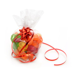 Gift of variety candy in package with ribbon and bow.