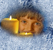 girl with candles looking through a frosted window