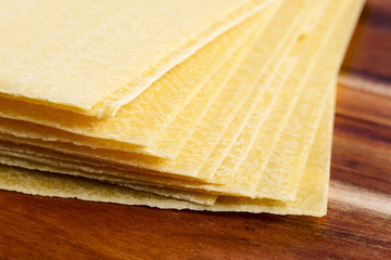 Uncooced lasagne pasta sheets on wooden table