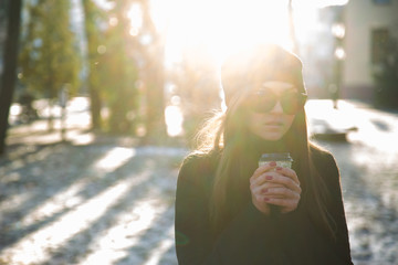 Girl with a coffee in the winter park