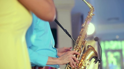 Black woman singer and her saxophone player performing on stage.