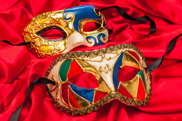 Two Mardi Gras Masks on red silk