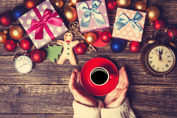 Female holding cup of coffee near christmas gifts on a table