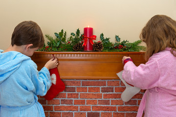 Children hanging stockings over the fireplace